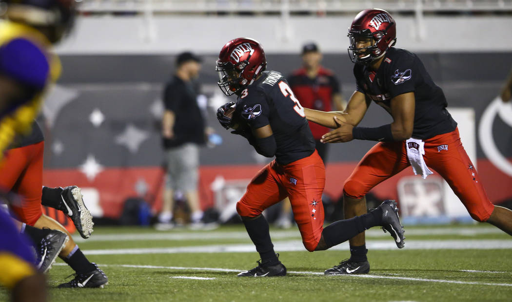 UNLV Rebels quarterback Armani Rogers (1) hands off the ball to UNLV Rebels running back Lexington Thomas (3) during the first half of a football game against the Prairie View A&M Panthers at ...