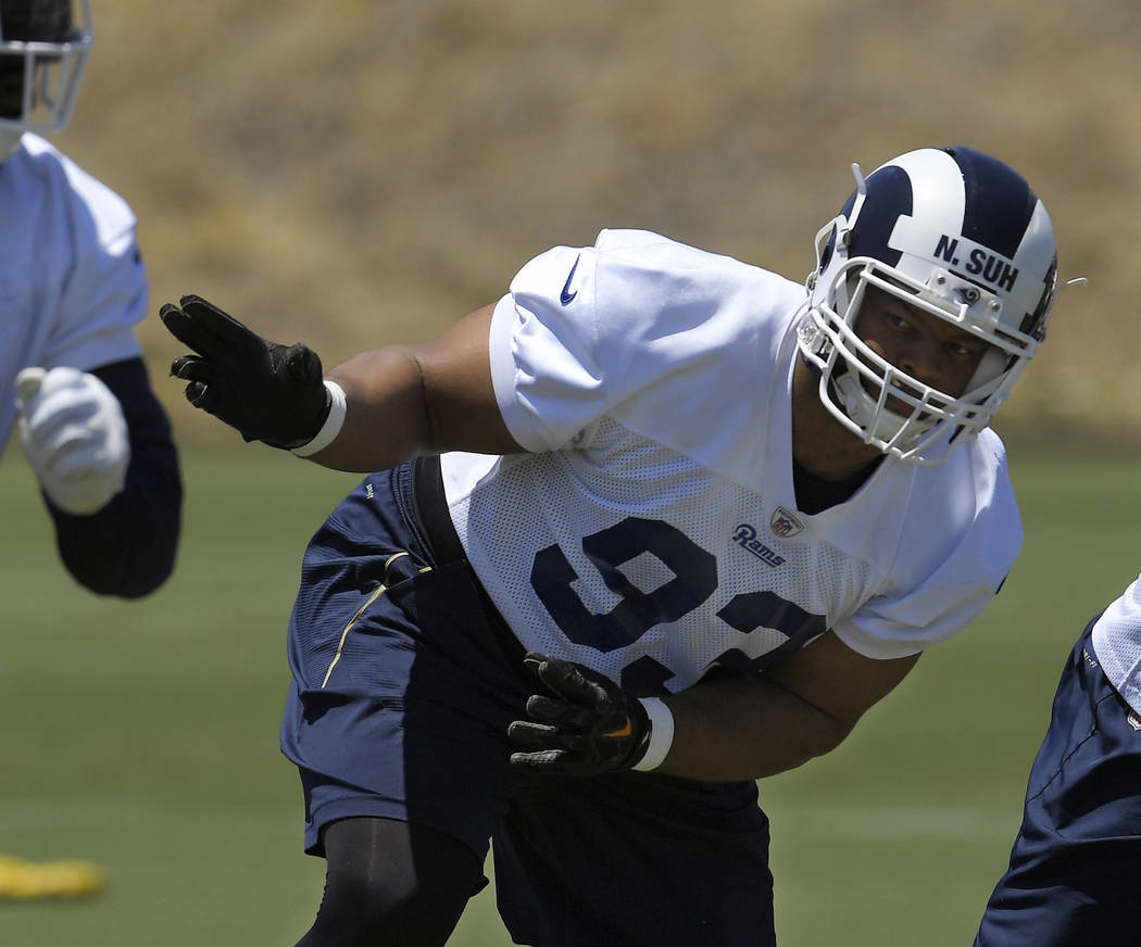 FILE - In this June 12, 2018, file photo, Los Angeles Rams defensive tackle Ndamukong Suh runs a play during practice at the NFL football team's minicamp in Thousand Oaks, Calif. Suh looks very co ...