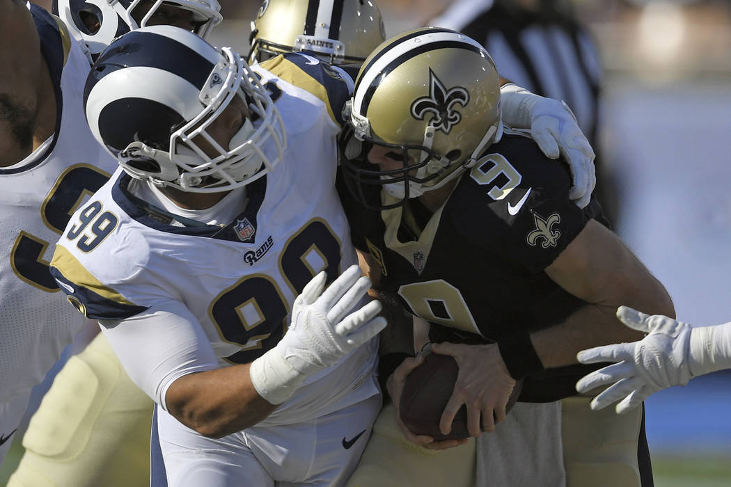 In this Nov. 26, 2017, file photo, New Orleans Saints quarterback Drew Brees, right, gets sacked by Los Angeles Rams defensive end Aaron Donald during the first half of an NFL football game,in Los ...