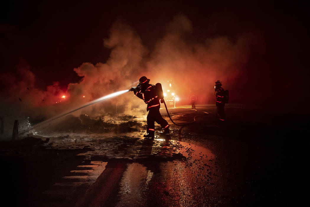 A firefighter sprays the smoldering remains of a vehicle on Interstate 5 as the Delta Fire burns in the Shasta-Trinity National Forest, Calif., on Wednesday, Sept. 5, 2018. Parked trucks lined mor ...