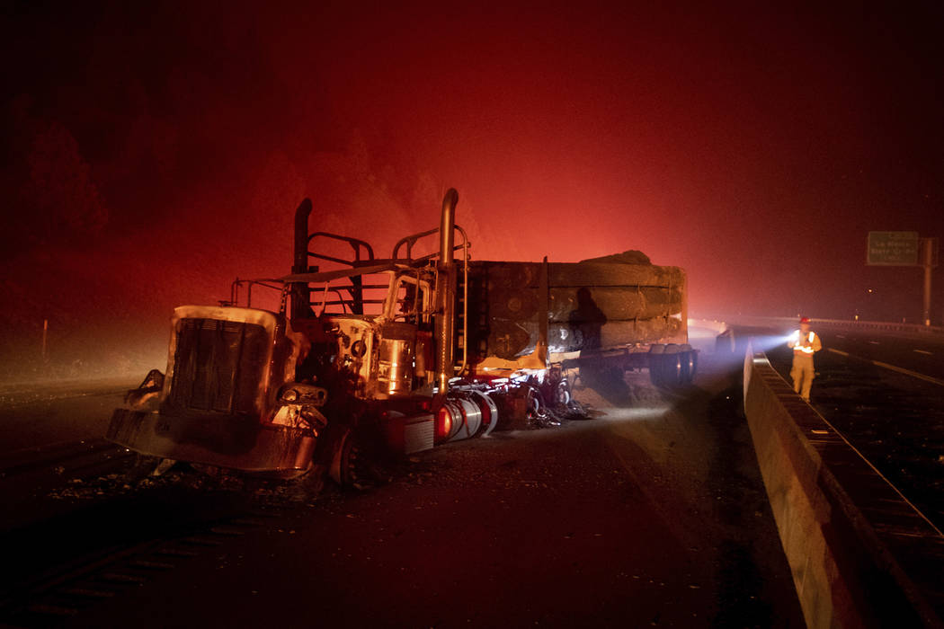 A scorched logging truck rests on Interstate 5 as the Delta Fire burns in the Shasta-Trinity National Forest, Calif., near Shasta Lake on Wednesday, Sept. 5, 2018. Parked trucks lined more than tw ...