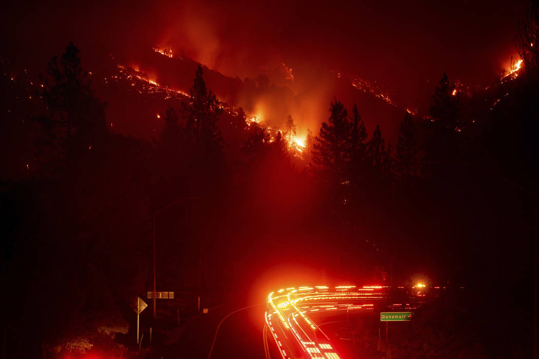 Fire trucks pass the Delta Fire burning in the Shasta-Trinity National Forest, Calif., on Wednesday, Sept. 5, 2018. Parked trucks lined more than two miles of Interstate 5 as both directions remai ...