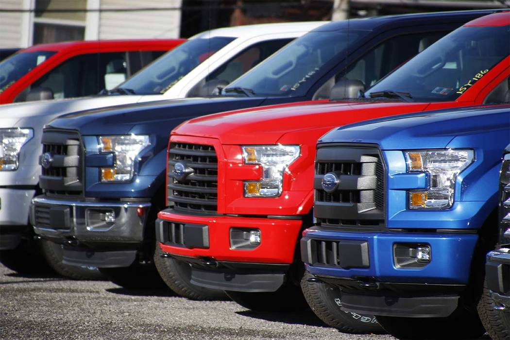 In this Nov. 19, 2015, file photo a row of 2015 Ford F-150 pickup trucks are parked on the sales lot at Butler County Ford in Butler, Pa. Under pressure from U.S. safety regulators, Ford is recall ...