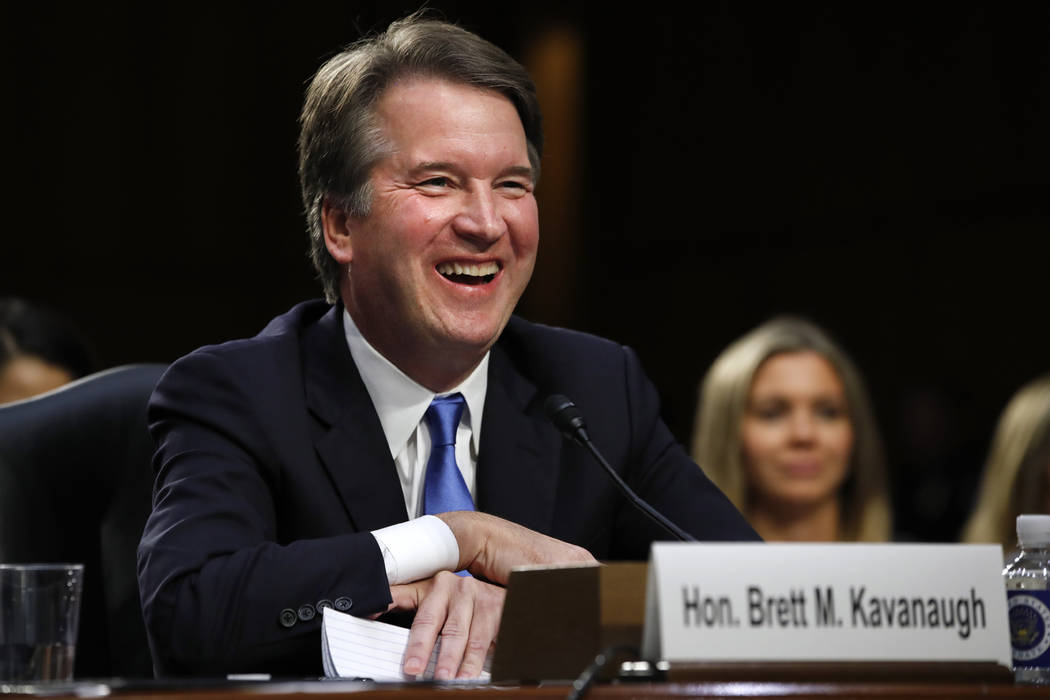 President Donald Trump's Supreme Court nominee, Brett Kavanaugh, laughs as Sen. Thom Tillis, R-N.C., makes closing remarks in the evening after the second day of his Senate Judiciary Committee con ...