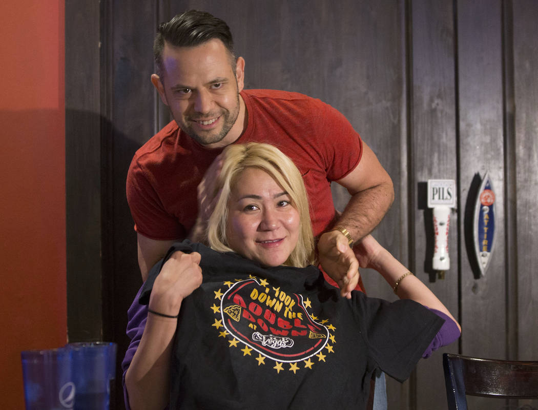 Las Vegas local and competitive eating champion Miki Sudo, bottom, gets her tee shirt from Dave Michel after completing the Double Down Pizza Challenge at Slice of Vegas on Thursday, Sept. 6, 2018 ...