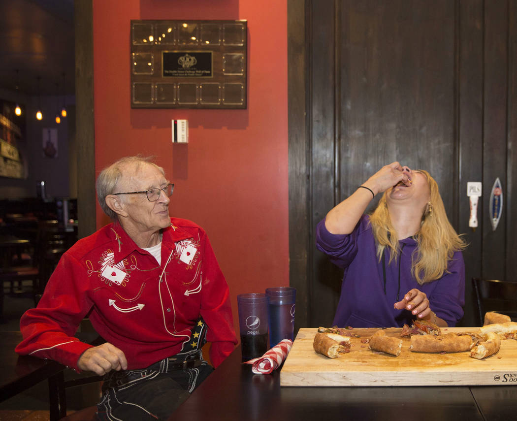 """Las Vegas local and competitive eating champion Miki Sudo, right, attempts to complete the Double Down Pizza Challenge with the support of fellow competitive eater and friend Rich """"The Locust ..."""