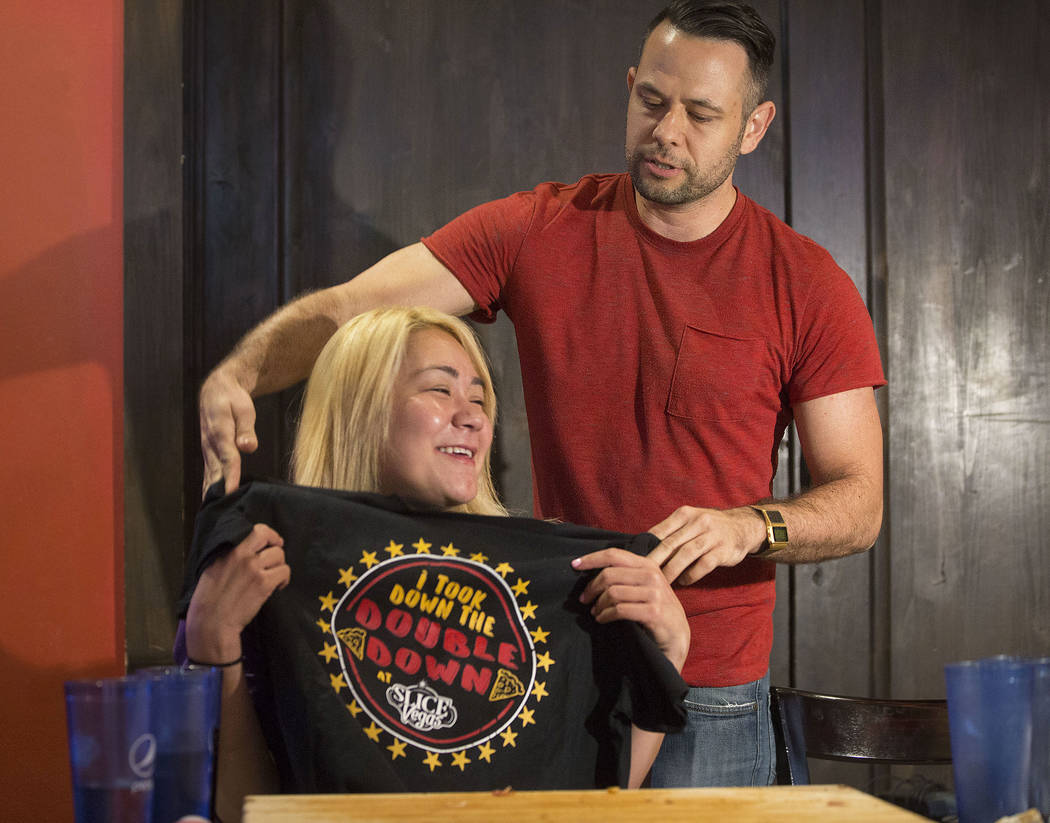 Las Vegas local and competitive eating champion Miki Sudo, left, gets her tee shirt from Dave Michel after completing the Double Down Pizza Challenge at Slice of Vegas on Thursday, Sept. 6, 2018, ...