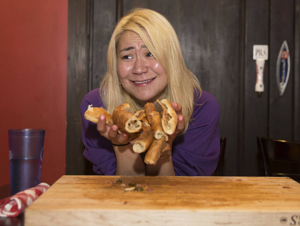 Las Vegas local and competitive eating champion Miki Sudo holds up the crust she still has to eat to complete the Double Down Pizza Challenge at Slice of Vegas on Thursday, Sept. 6, 2018, at Manda ...