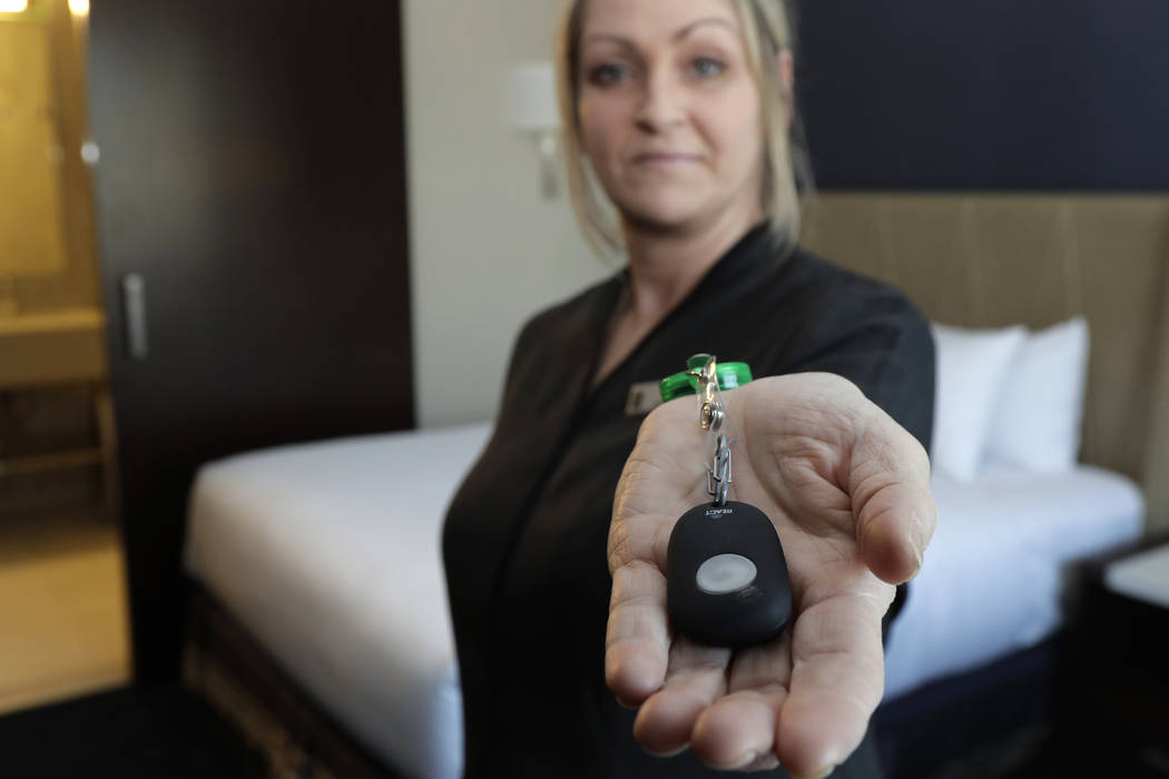 Rani Accettola, a housekeeper at the Embassy Suites by Hilton hotel in Seattle's Pioneer Square neighborhood, poses for a photo while holding a device that lets her push a button and summon help i ...