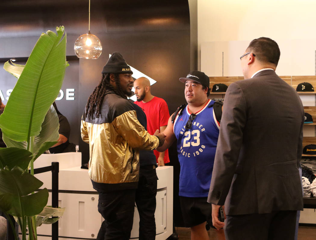 Oakland Raiders running back Marshawn Lynch, left, shakes hands with a fan during the grand opening of his store 'Beastmode' in Town Square in Las Vegas, Saturday, Sept. 1, 2018. Heidi Fang Las Ve ...