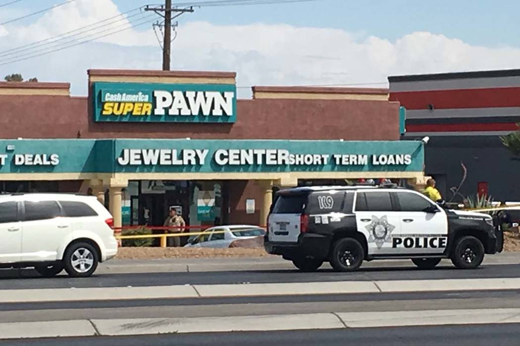 A Metro police officer is posted in front of a Cash America Super Pawn store at 1150 S. Rainbow Blvd. in Las Vegas as officers investigate an officer-involved shooting in the area. (Michael Scott ...