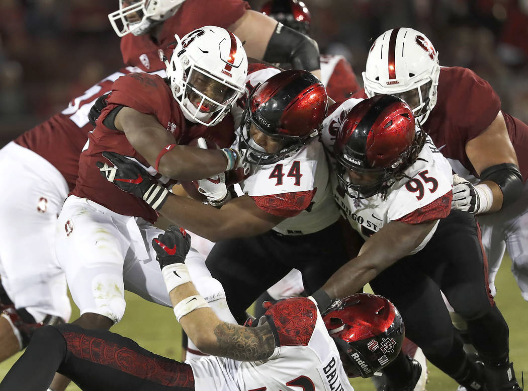 Stanford running back Bryce Love, left, is tackled by San Diego State linebacker Kyahva Tezino (44) and defensive lineman Noble Hall (95) during the second half of an NCAA college football game Fr ...