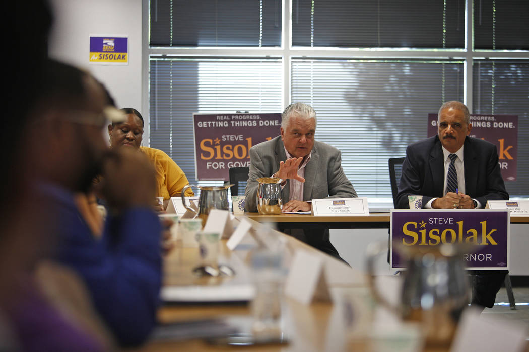Commissioner Steve Sisolak speaks at a roundtable event about criminal justice reform next to former Attorney General Eric Holder at the Service Employees International Union Local 1107 offices in ...