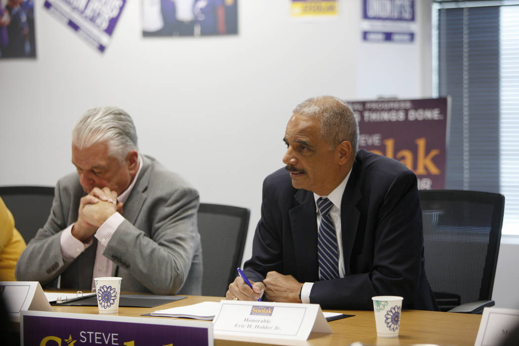 Former Attorney General Eric Holder, right, speaks at a roundtable event about criminal justice reform next to former Commissioner Steve Sisolak at the Service Employees International Union Local ...