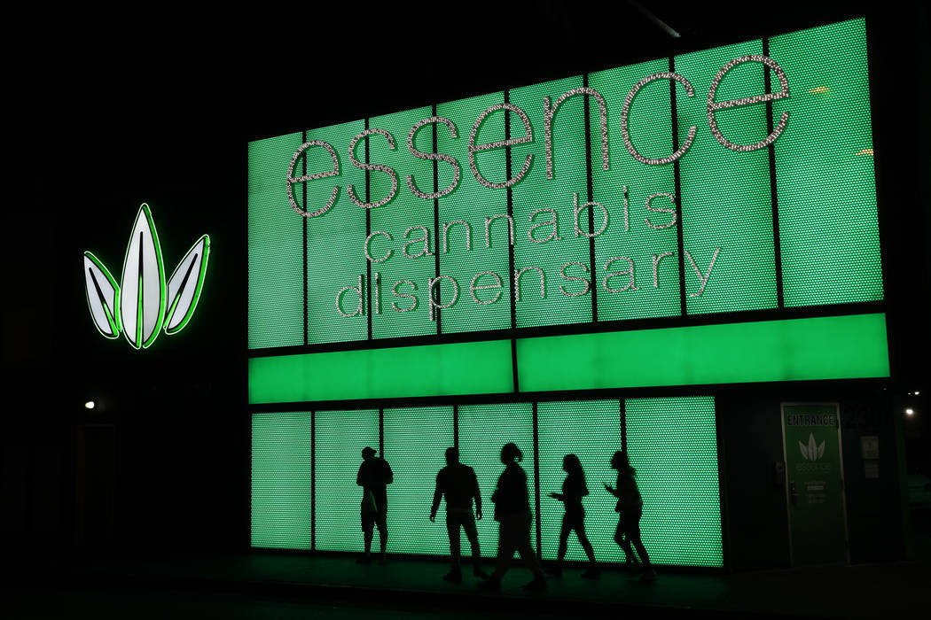 File - In this April 16, 2018, file photo, people stand outside after shopping at the Essence cannabis dispensary in Las Vegas. (AP Photo/John Locher)