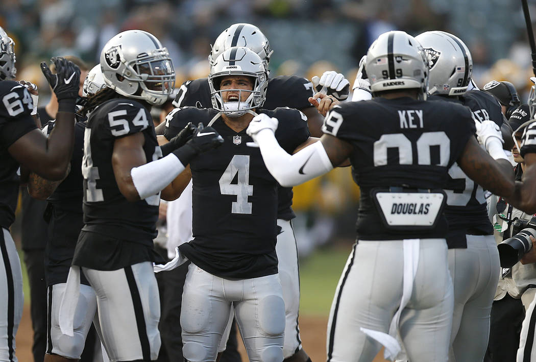 Oakland Raiders quarterback Derek Carr (4) stretches with teammates before an NFL preseason football game against the Green Bay Packers in Oakland, Calif., Friday, Aug. 24, 2018. (AP Photo/D. Ross ...