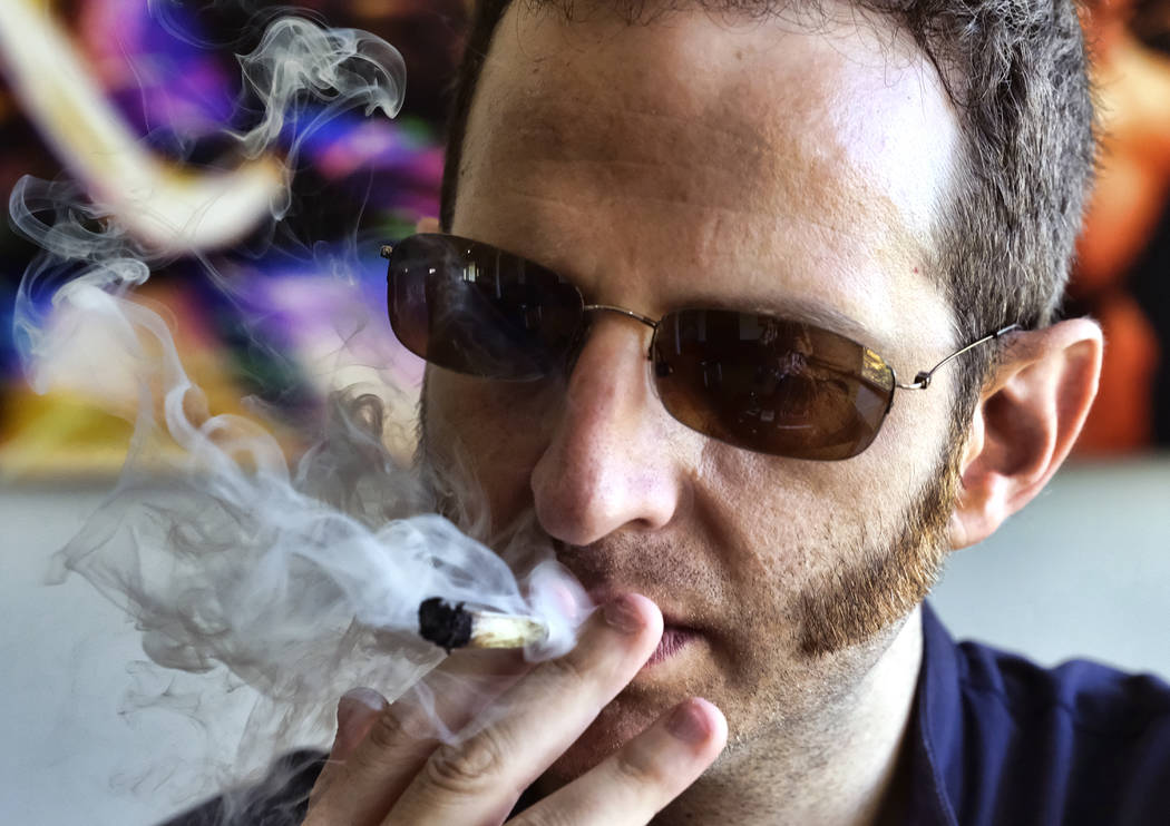 In this Saturday, Aug. 25, 2018 photo, Judd Weiss takes a puff of a pre-rolled marijuana cigarette at his house in the Bel Air section of Los Angeles. Weiss, CEO and founder of cannabis company Li ...