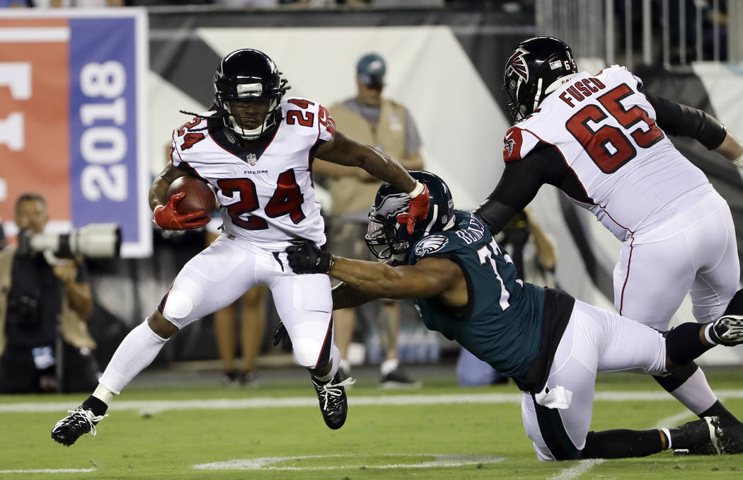 Atlanta Falcons' Devonta Freeman (24) tries to get away from Philadelphia Eagles' Michael Bennett (77) during the first half of an NFL football game Thursday, Sept. 6, 2018, in Philadelphia. (AP P ...