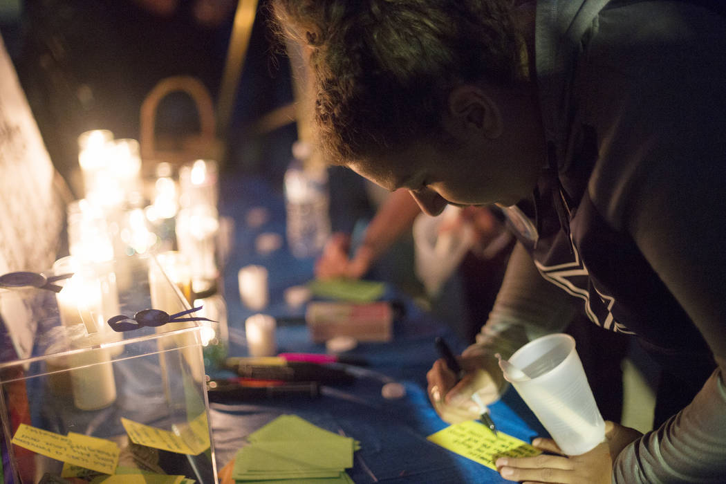Emily Hopson writes a note to the family of 8-year-old Levi Echenique at a vigil at Paradise Park in Las Vegas, Sunday, Sept. 9, 2018. Echenique was killed in a car crash on Aug. 31. His parents B ...