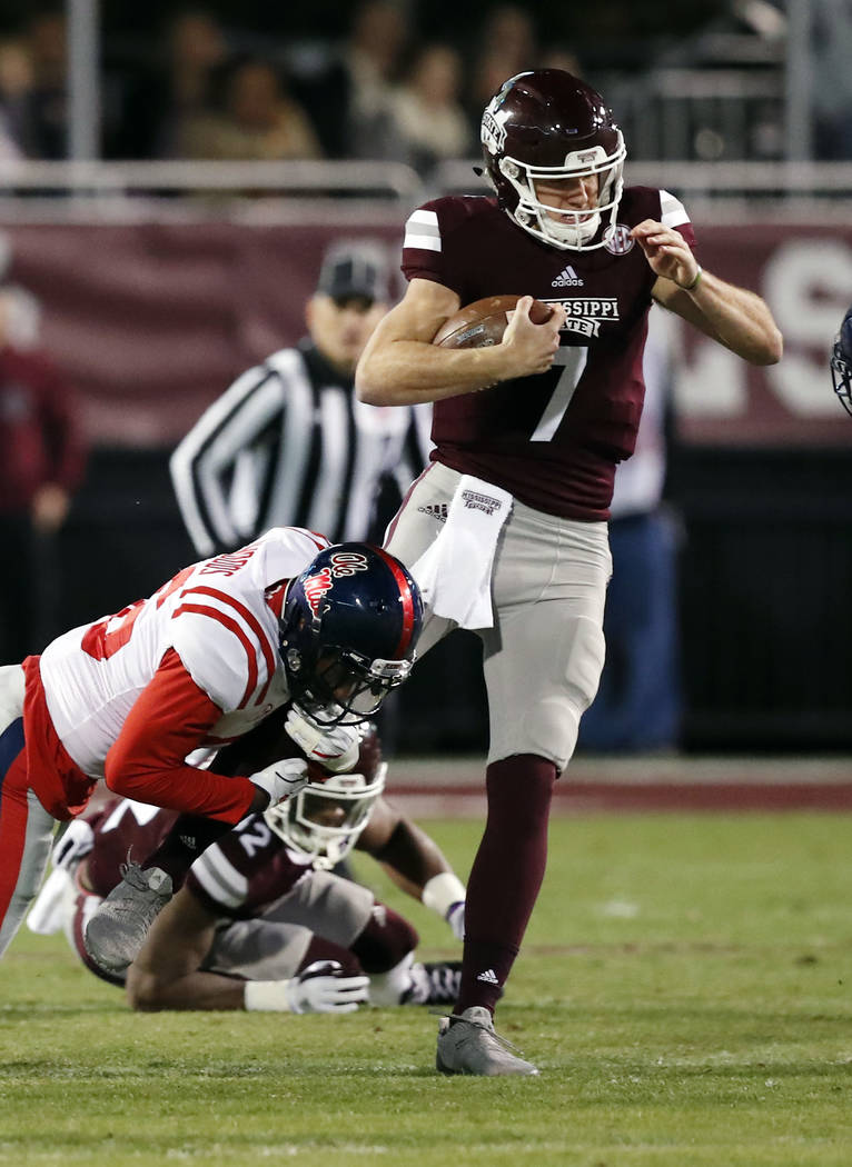 Mississippi State quarterback Nick Fitzgerald (7) is tackled by Mississippi's Zedrick Woods during the first half of an NCAA college football game in Starkville, Miss., Thursday, Nov. 23, 2017. (A ...