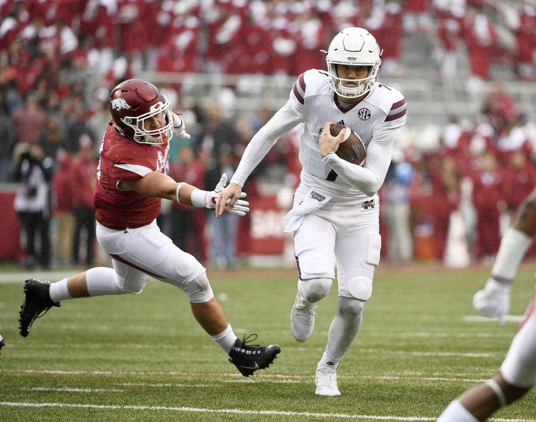 FILE - In this Nov. 18, 2017, file photo, Mississippi State quarterback Nick Fitzgerald slips past Arkansas defender Grant Morgan to score a touchdown during the first half of an NCAA college foot ...