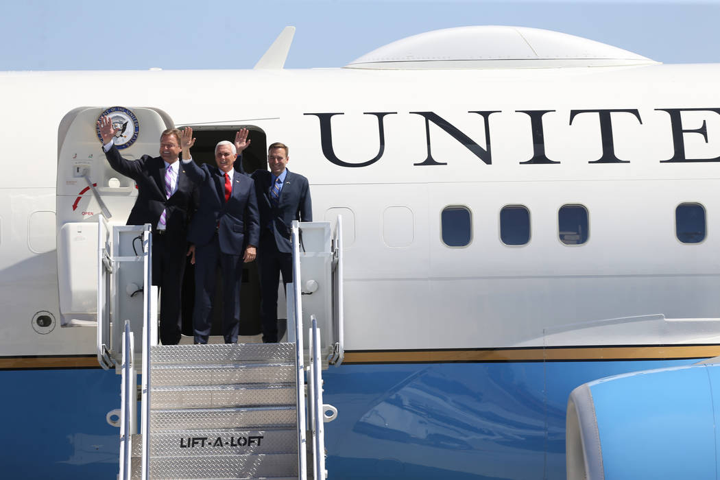Vice President Mike Pence, center, with U.S. Sen. Dean Heller, left, and Attorney General Adam Laxalt, exit Air Force Two after landing at Nellis Air Force Base in Las Vegas Friday, Sept. 7, 2018. ...