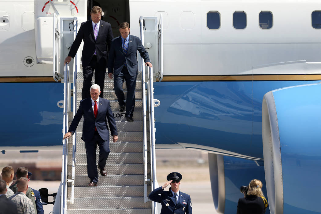 Vice President Mike Pence, bottom, with U.S. Sen. Dean Heller, top left, and Attorney General Adam Laxalt, exit Air Force Two after landing at Nellis Air Force Base in Las Vegas Friday, Sept. 7, 2 ...