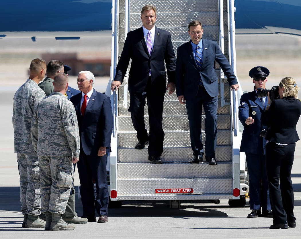 Vice President Mike Pence meets with officials as U.S. Sen. Dean Heller, top left, and Attorney General Adam Laxalt exit Air Force Two after landing at Nellis Air Force Base in Las Vegas Friday, S ...