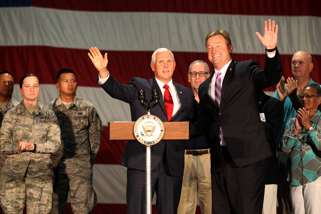 Vice President Mike Pence and U.S. Sen. Dean Heller acknowledge the crowd after speaking with airmen and veterans in the Thunderbirds hanger at Nellis Air Force Base in Las Vegas Friday, Sept. 7, ...