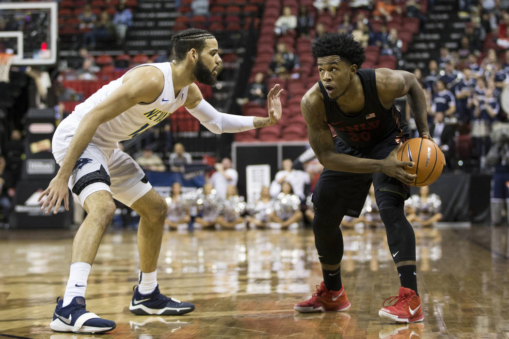 UNLV Rebels guard Jovan Mooring (30) is guarded by Nevada Wolf Pack forward Cody Martin (11) in the second half of the Mountain West Conference men's basketball tournament game at the Thomas & ...