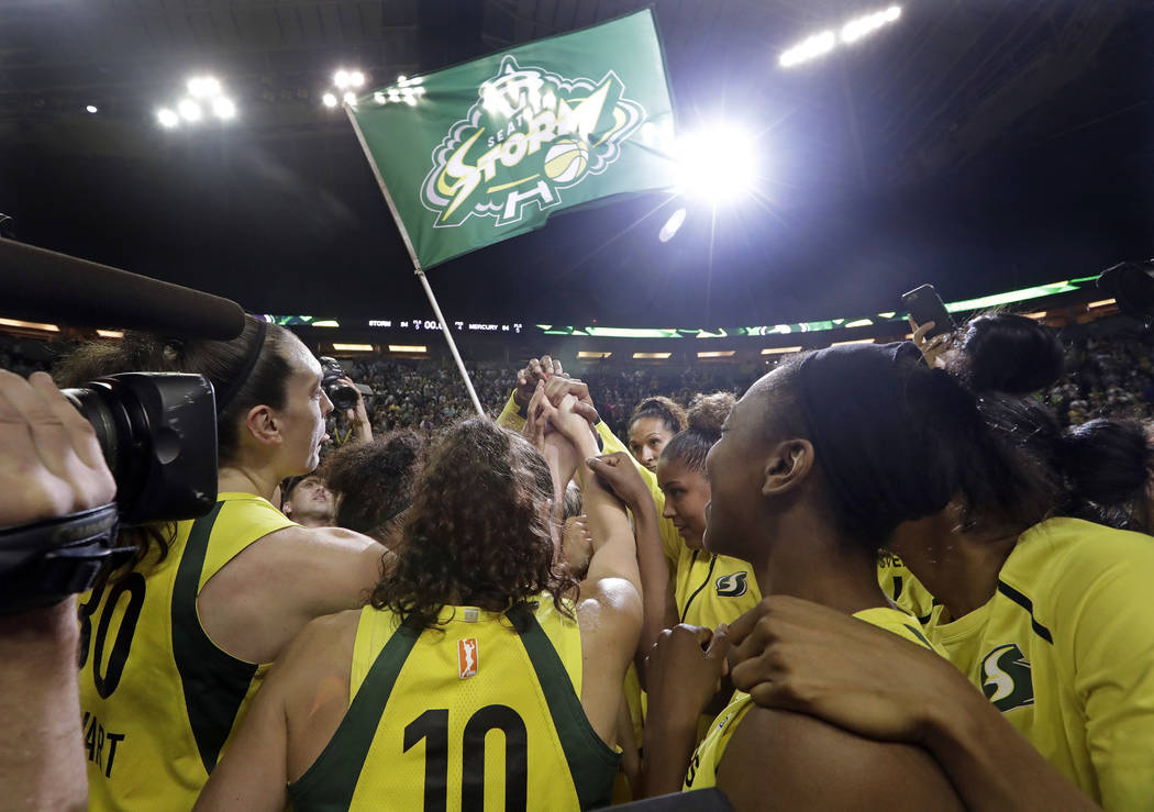 Seattle Storm players huddle in celebration after beating the Phoenix Mercury in a semifinal basketball playoff game Tuesday, Sept. 4, 2018, in Seattle. The Storm won 94-84 and they advance to the ...