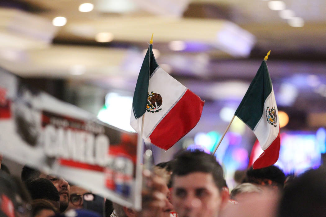 "People wave Mexican flags during a boxing ""Grand Arrivals"" event for Gennady Golovkin and Saul ""Canelo"" Alvarez at the MGM Grand hotel-casino in Las Vegas, Tuesday, Sept. 11, 2 ..."
