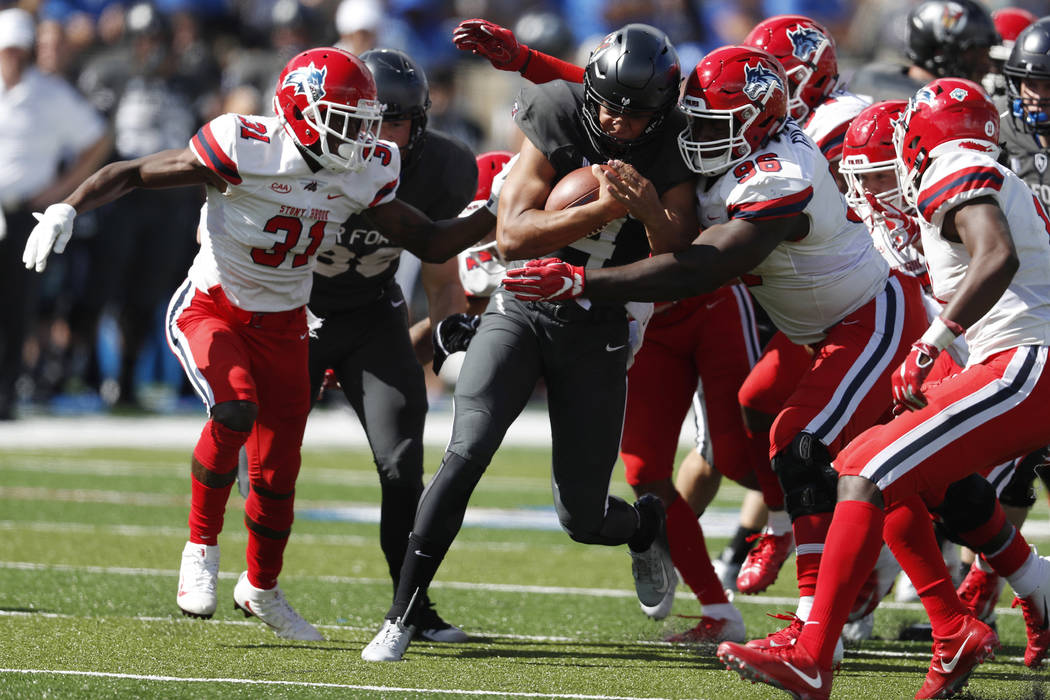 Air Force quarterback Isaiah Sanders, second from left, is stopped after a short gain by, from left, Stony Brook defensive back Kareem Gaulden, defensive lineman Odean Gilzene and defensive back G ...
