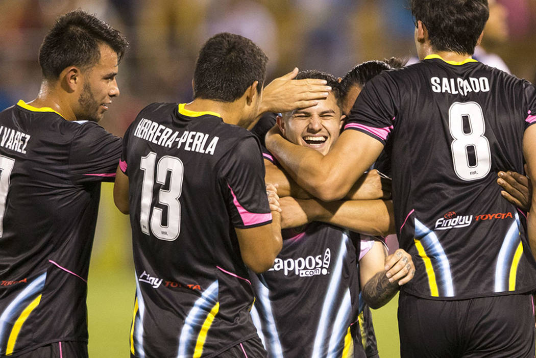Las Vegas Lights FC midfielder Raul Mendiola (40), center, is swarmed by teammates after scoring a goal against Fresno FC during the second half of a United Soccer League match at Cashman Field in ...