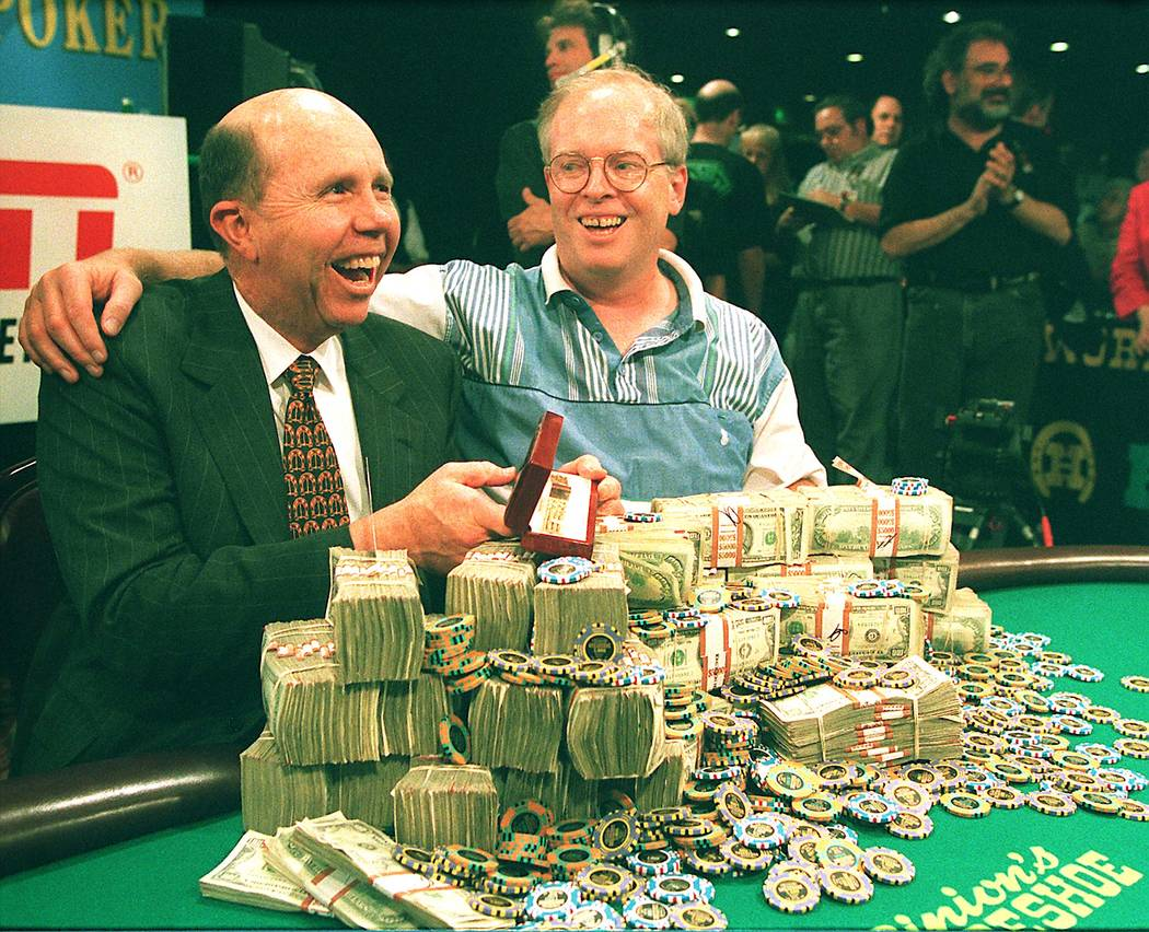 Jack Binion, left, and Dan Harrington of Downey, Calif., look over a mountain of cash and chips on Thursday after Harrington won the 1995 World Series of Poker championship event at Binion's Hors ...