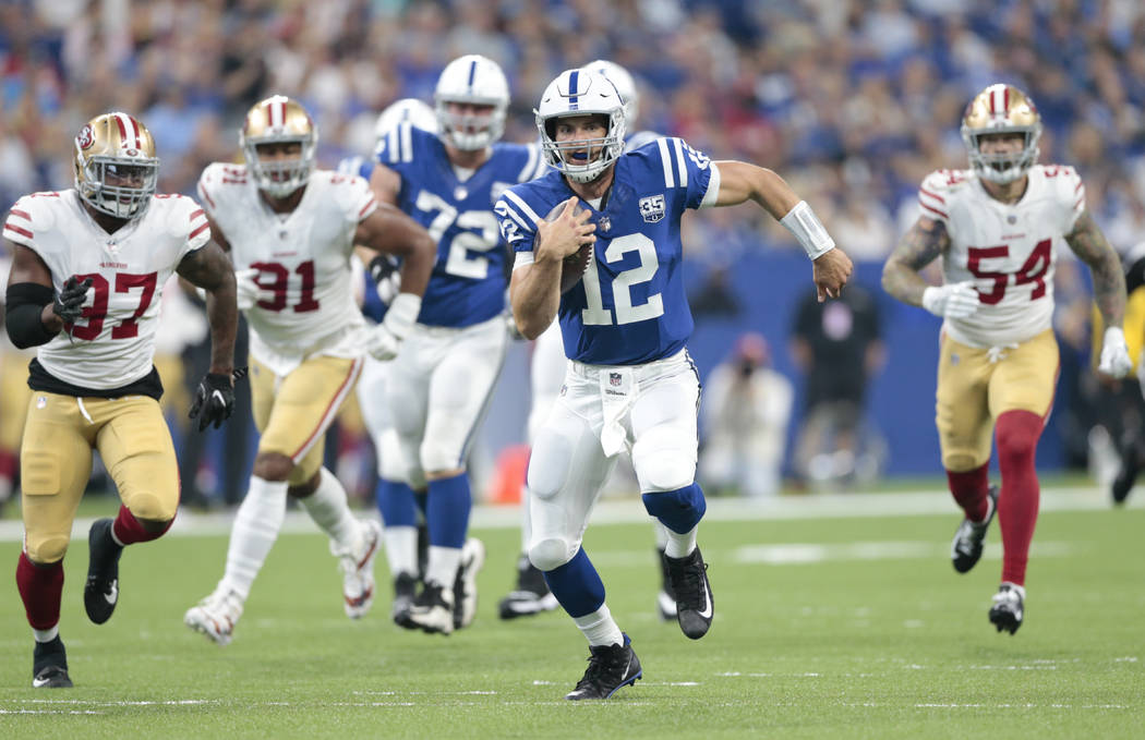 Indianapolis Colts quarterback Andrew Luck (12) scrambles away from San Francisco 49ers linebacker Dekoda Watson (97), defensive end Arik Armstead (91) and defensive end Cassius Marsh (54) in the ...