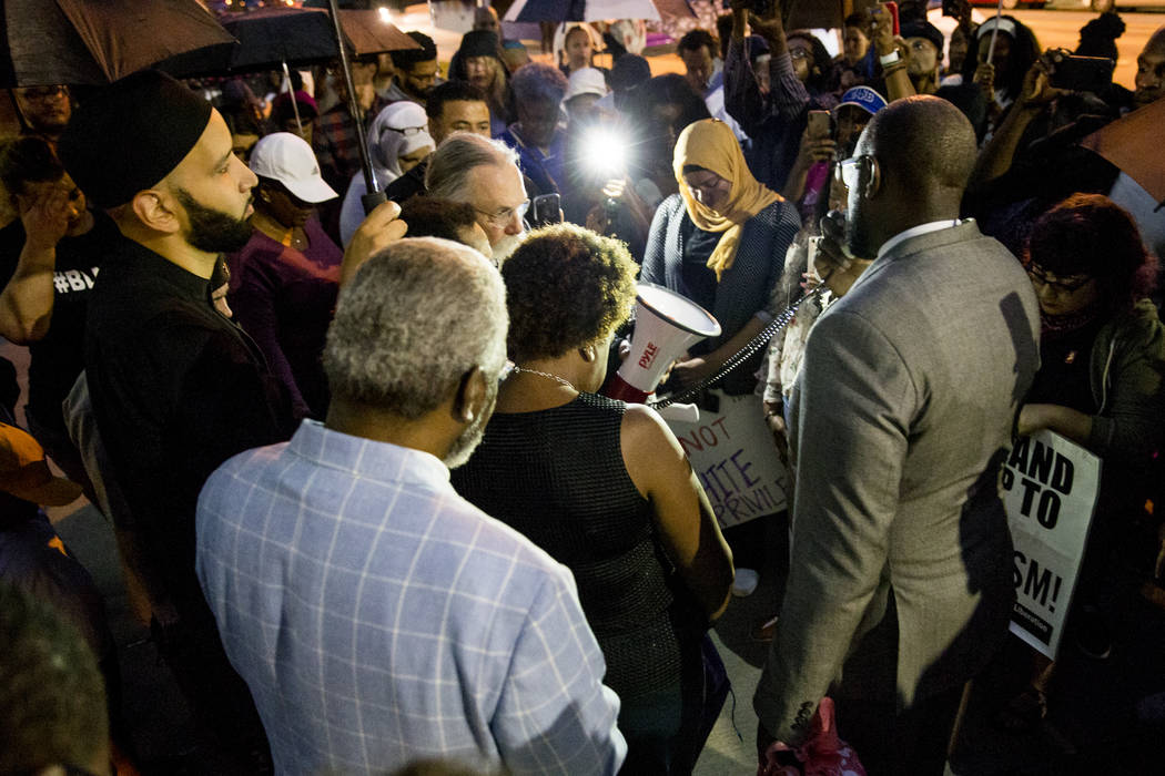 Pastor Michael W. Waters leads a prayer following a Mothers Against Police Brutality candlelight vigil for Botham Jean at the Jack Evans Police Headquarters on Friday, Sept. 7, 2018, in Dallas. Au ...