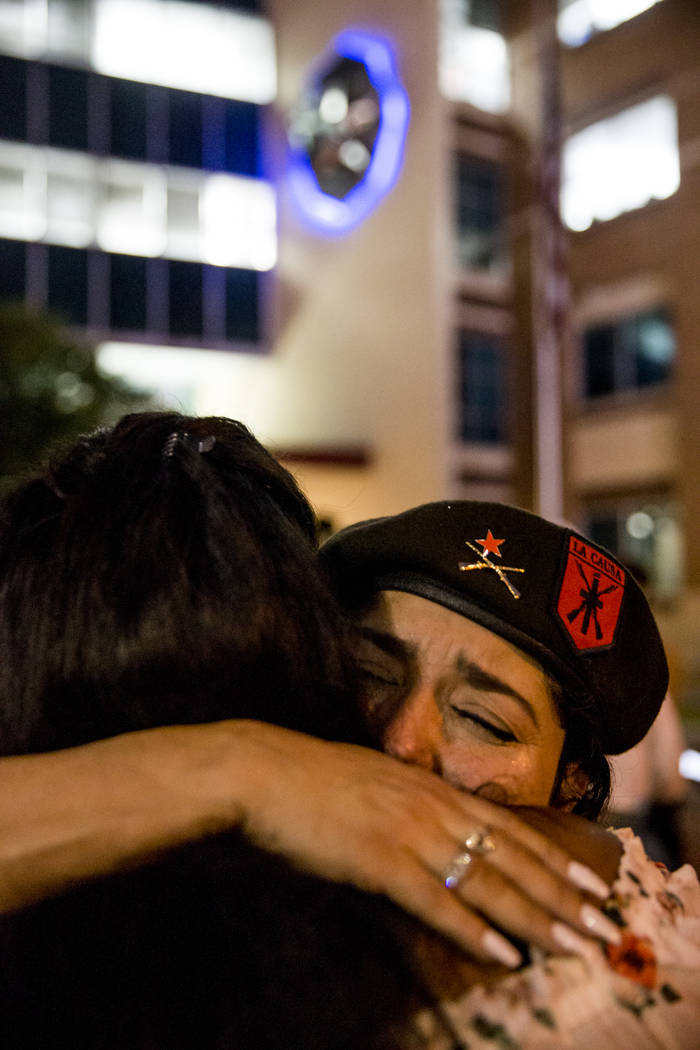Debra Mendoza, national prime minister of the Brown Berets, embraces an attendant during a Mothers Against Police Brutality candlelight vigil for Botham Jean at the Jack Evans Police Headquarters ...