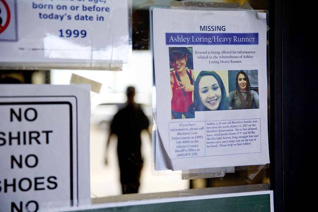 A missing poster for Ashley HeavyRunner Loring is posted to the entrance of a grocery store on the Blackfeet Indian Reservation in Browning, Mont., Thursday, July 12, 2018. (AP Photo/David Goldman)