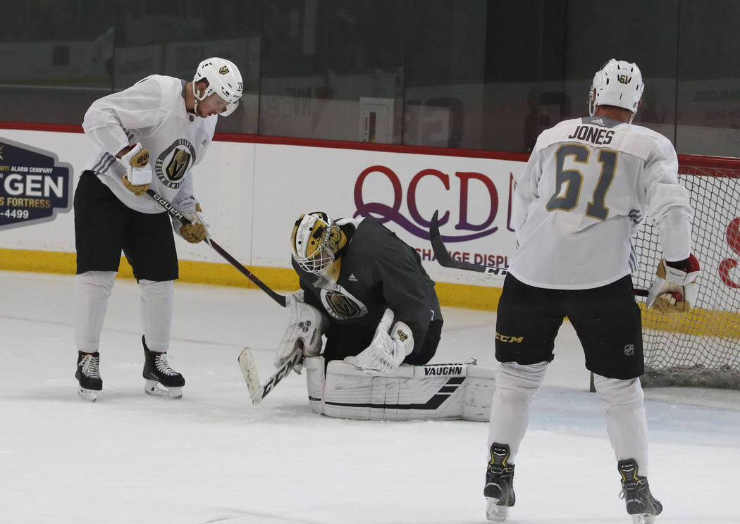 Golden Knights goalie Jiri Patera blocks a shot from forward Lucas Elvenes, left, as forward Ben Jones (61) looks on during Knights rookie camp practice at City National Arena in Las Vegas on Frid ...