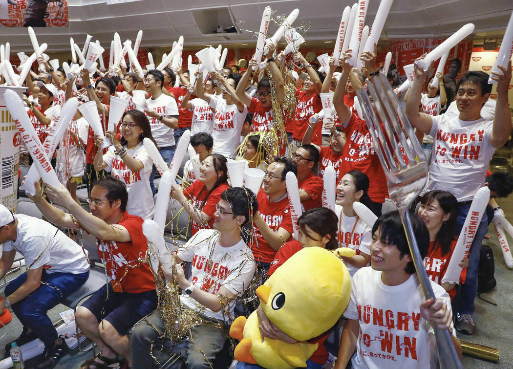 Employees of Nissin Food Products Co., celebrate after the victory of Japan's Naomi Osaka, as they watch the live broadcast of the U.S. Open tennis women's final between Serena Williams of the U.S ...