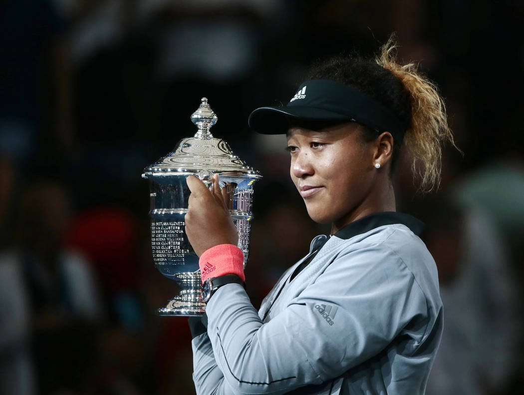 Naomi Osaka, of Japan, holds the trophy after defeating Serena Williams in the women's final of the U.S. Open tennis tournament, Saturday, Sept. 8, 2018, in New York. (AP Photo/Andres Kudacki)