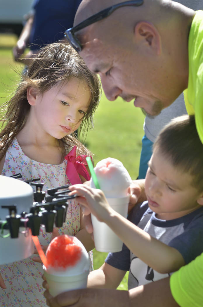 Olivia Amescua, left, watches while her father Stevie helps her brother Sonny add flavoring to a cup of shaved ice during the Armed Forces Military Veterans and First Responders Appreciation Day a ...