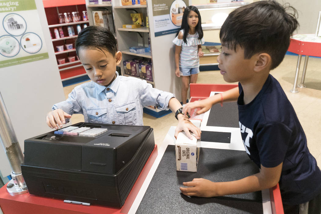 Nic Faustin, 6, left, pretends to sell oatmeal to Kyle Aiden, 7, at the Eco City exhibit at the Discovery Children's Museum during the museum's birthday in Las Vegas, Sunday, Sept. 9, 2018. (Marcu ...