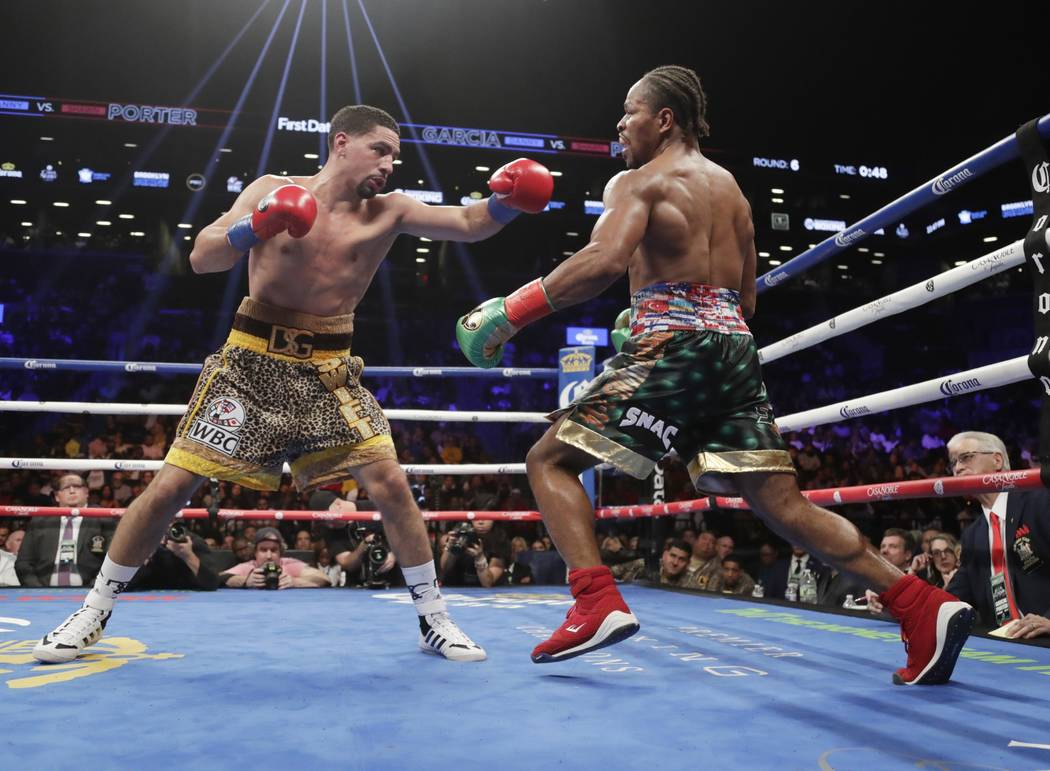 Shawn Porter, right, avoids a punch from Danny Garcia during the sixth round of a WBC welterweight championship boxing match Saturday, Sept. 8, 2018, in New York. Porter won the fight. (AP Photo/F ...