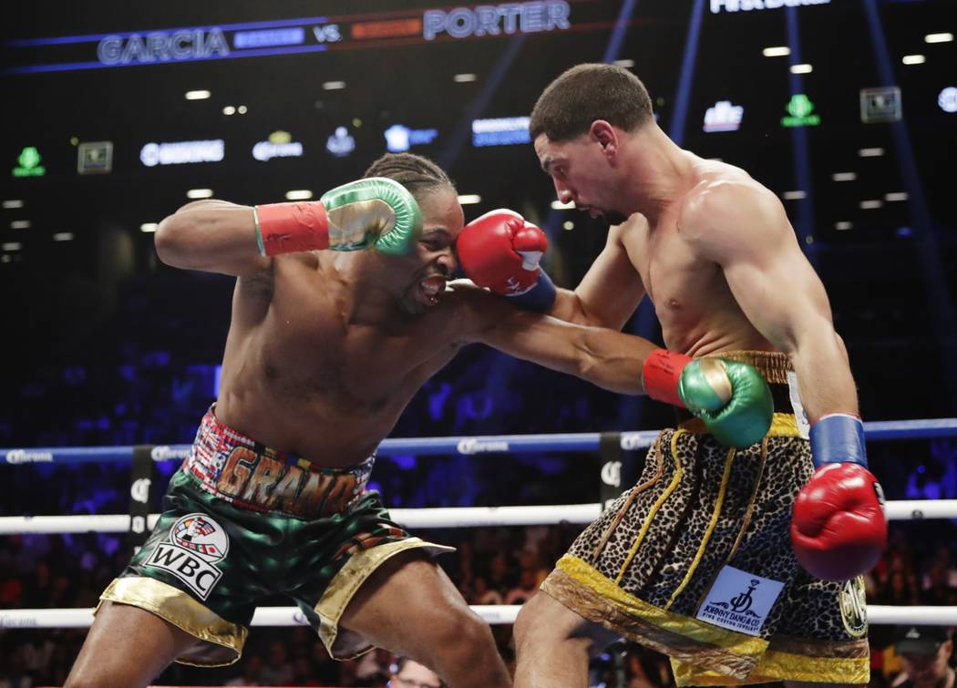 Shawn Porter, left, fights Danny Garcia during the second round of a WBC welterweight championship boxing match Saturday, Sept. 8, 2018, in New York. Porter won the fight. (AP Photo/Frank Franklin II)