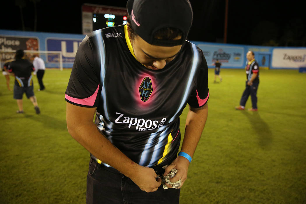 Marck Garcia of Las Vegas shows a piece of the $5,000 he collected from a helicopter cash drop at half time during an USL soccer game between the Las Vegas Lights and LA galaxy II at Cashman Field ...