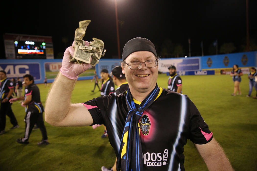 David Weigant of Las Vegas shows a piece of the $5,000 he collected from a helicopter cash drop at half time during an USL soccer game between the Las Vegas Lights and LA galaxy II at Cashman Fiel ...
