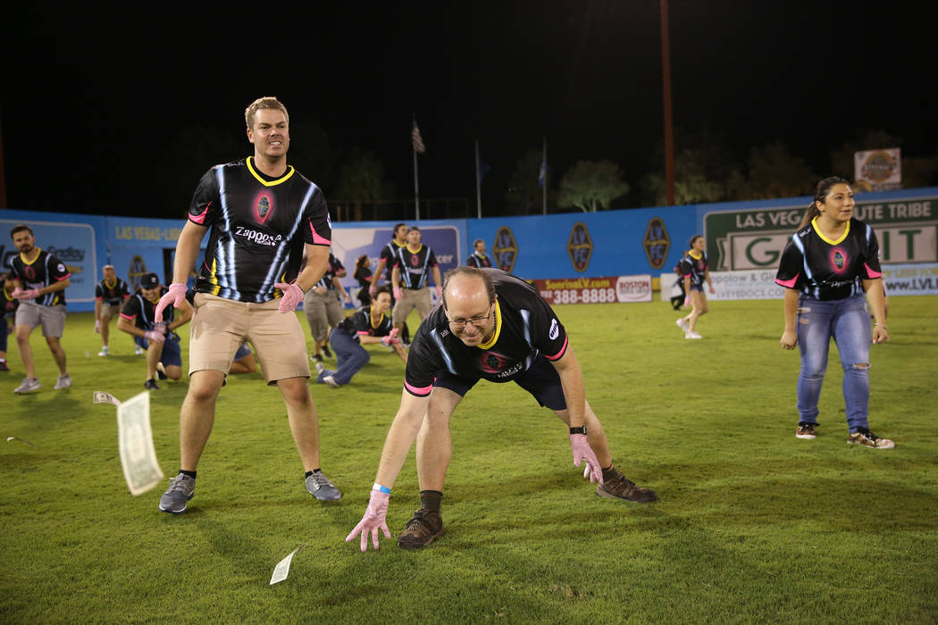 Fans rush to collect a piece of the $5,000 dropped from a helicopter at half time during an USL soccer game between the Las Vegas Lights and LA galaxy II at Cashman Field in Las Vegas, Saturday, S ...