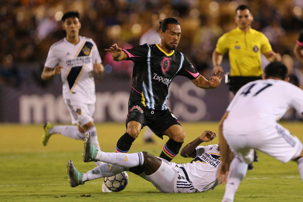 Las Vegas Lights' Daigo Kobayashi (44) loses the ball to a tackled from LA Galaxy II's Geoffrey Acheampong (44) during the first half of an USL game at Cashman Field in Las Vegas, Saturday, Sept. ...